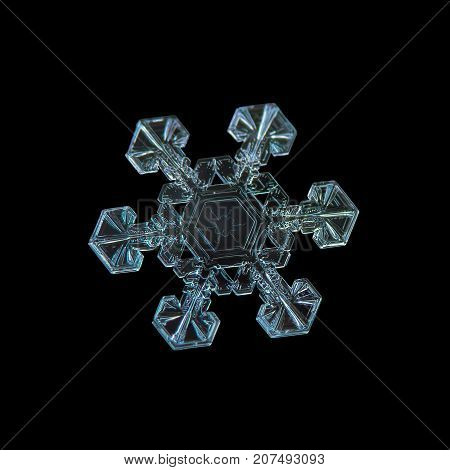 Snowflake isolated on black background. Macro photo of real snow crystal: large star plate with six short, simple arms, fine hexagonal symmetry and unusual pattern inside central hexagon.
