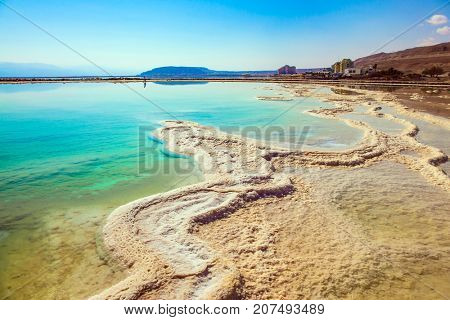 The concept of medical and ecological tourism. The evaporated salt on the shallow coast of the Dead Sea. Therapeutic Dead Sea, Israel