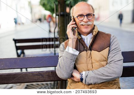 Mature Man Talking On Phone While Sitting On The Bench In The City Street