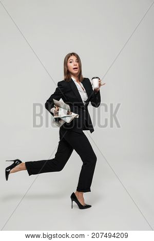 Portrait of a funny busy businesswoman in suit holding take away coffee cup and a newspaper while running late and looking at camera isolated over white background