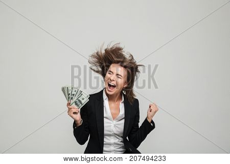 Portrait of a happy thrilled businesswoman in suit holding bunch of money banknotes and celebrating isolated over white background