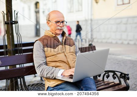 Senior Handsome Man Using Laptop In The Street On The Bench