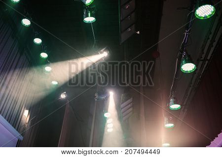 Color light in the concert stage. Color flood light on the ceiling. Soffits light illuminate the scene. Electric light. Light equipment on stage for a concert. Red and blue light