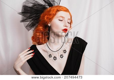 Glamour woman with pale skin and a glamour hairdo with beautiful precious glamour ornaments from white beads. Beautiful glamour girl with red lips. Glamour model. Glamour make up
