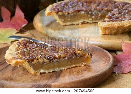 Closeup of a slice of pecan pie with autumn leaves