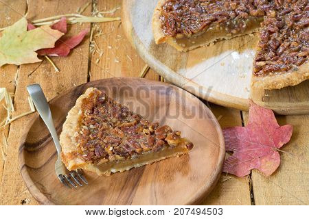 Slice of pecan pie on a wooden surface with autumn leaves