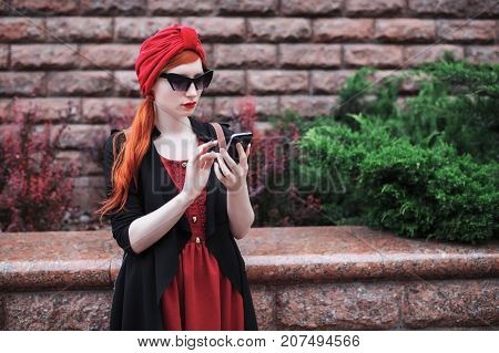Stylish red-haired girl in sunglasses and in a red turban with a smartphone in her hands. A woman with a new smartphone device. Smartphone in hands. To look at smartphone. Black smartphone, Fashion concept with smartphone