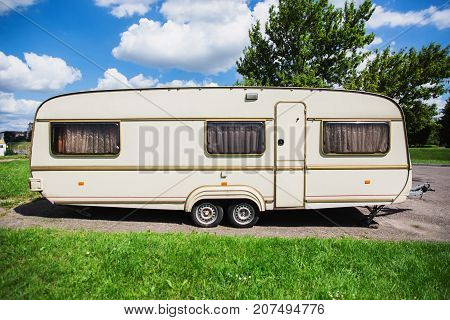 A new trailer stands on a summer background. Trailer on the street. Gray trailer. Trailer on wheels