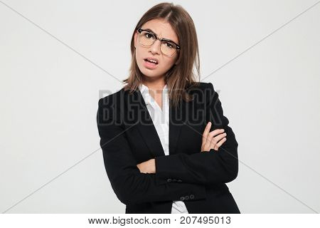 Portrait of a pretty frustrated businesswoman in suit and eyeglasses standing with arms folded and looking at camera isolated over white background
