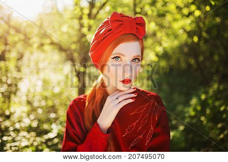 A woman with pale skin and long red hair a red dress and a turban on a summer background. A girl with turban and red. nails. Turban on head. Female style. Retro style. Vintage style. Fashion style.