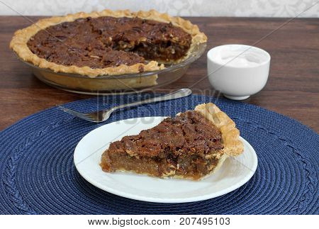 A slice of fresh baked homemade pecan pie with a whole pecan pie in the background. Bowl of whipped cream to the side.