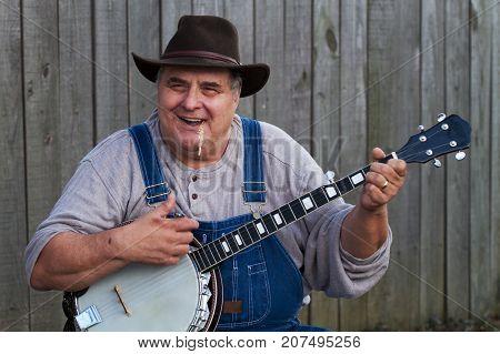 a banjo player man playing music outside.