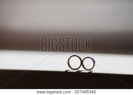 Wedding rings lie on a window on a dark white background.  Golden rings. Two rings on window. Couple of rings on white background.