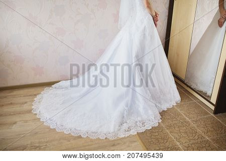 The hem of the wedding clothing lies on the wooden floor. The bride is standing in a wedding dress. Wedding clothing. Woman clothing. Nice clothing. Fashion clothing on wood floor.
