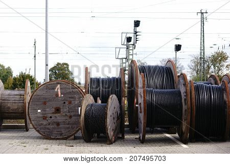 Large wooden cable pulleys with electric cables for rail transport.