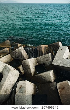 View of plenty of concrete blocks in water of sea creating breakwater on background of sea space.