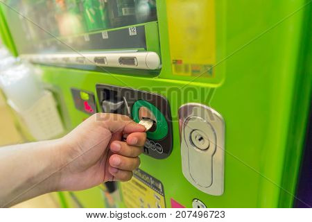 close up the hand is insert coin in vendor machine