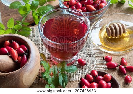A Cup Of Rose Hip Tea With Fresh Rose Hips