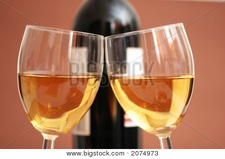 Two Wine Glasses And The Bottle At Background