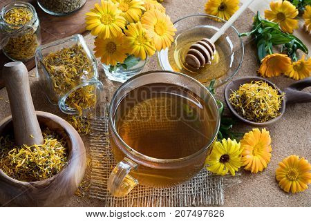 A Cup Of Calendula Tea With Calendula In The Background
