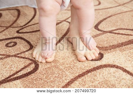 Mother and baby legs. First steps concept