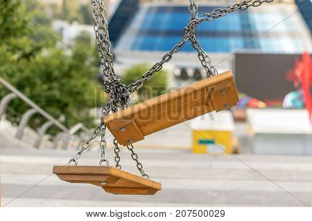 Swings, carousels with intricate chains against the background of the city with modern architecture
