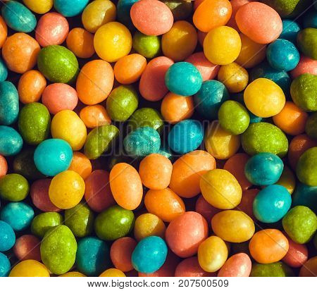 Heap of candy confections small many green, yellow, blue colors. Bright texture and round forms of sweets in sugar.