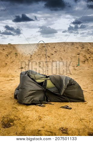 brown broken camping tent on the beach at the stormy weather