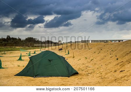 green tourist tent on the sand at stormy weather