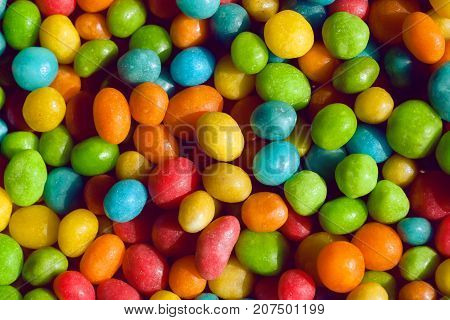 Tasty candy decoration background. Heap of colors candies for kids with small green yellow blue sweets.