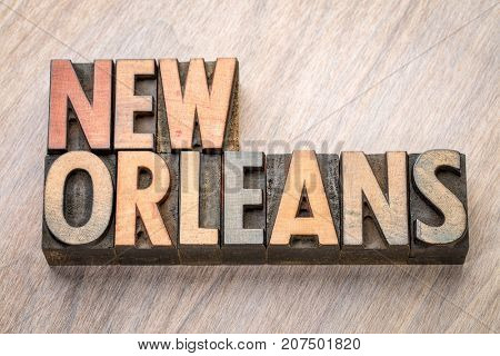 New Orleans word abstract in vintage  letterpress wood type against grained wooden background