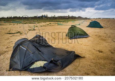 blue broken camping tent on the beach at the stormy weather and good tent at back