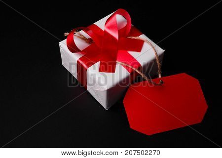 Close-up of red tag is attached to a white gift box with a red ribbon on a black background.