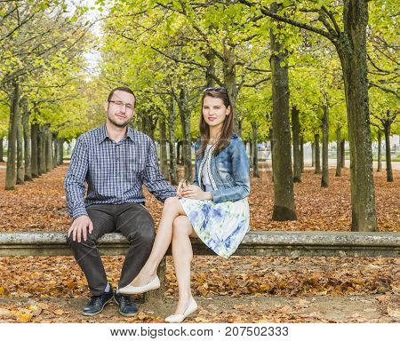 Lovely couple sitting together on a stone bench in a park in autumn.