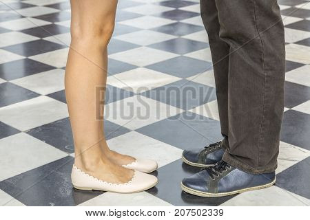 Image of legs of a couple standing face to face on a black and white squared marble floor.