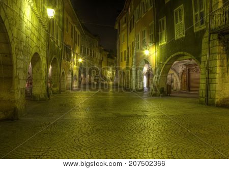 Nice illumination on an old paved street located in the historical downtown of Annecy in France