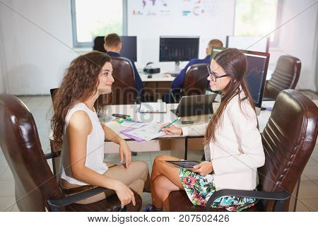 Close-up of two young cheerful business women who make a schedule sitting at a table.