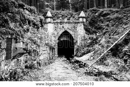 Upper entrance to tunnel of historical Schwarzenberg shipping canal, Sumava Mountains, Czech Republic. Black and white image.