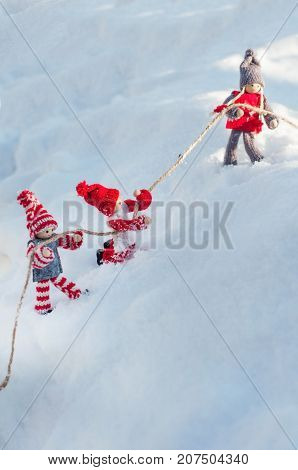 doll toy snow rope rescue winter white day child friendship help danger slopethree wooden dolls on a snowy clinging to a rope on a winter day