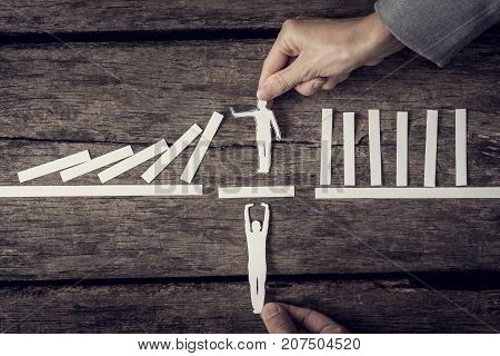 Two Businesspeople Supporting Cutout Of A Man Stopping The Domino Effect