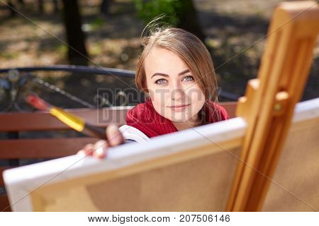Artist in a red scarf painting a picture with a pencil in the park. Beautiful woman painter picture. Young girl painting autumn landscape.
