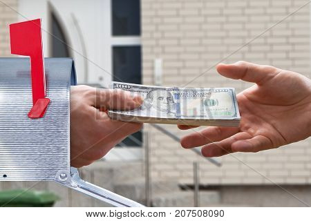 Close-up Of A Person's Hand Giving Money From Letter Box