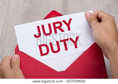 Close-up Of A Human Hand Holding Jury Duty Document In Red Envelope