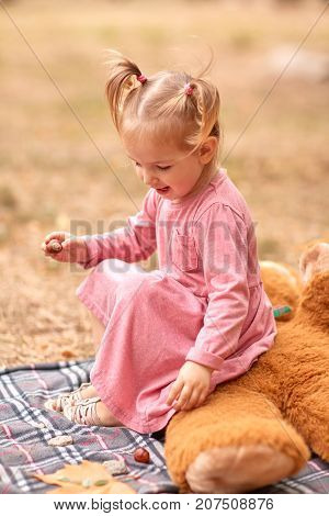 Close-up of a beautiful little girl in a pink dress playining in the fresh air