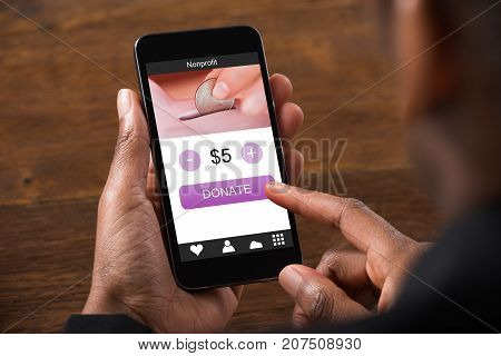 Close-up Of African Business Man Holding Mobile Phone Donating Money Online Against Wooden Table