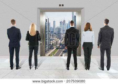 Rear View Of Businessman And Businesswoman Looking At Modern Elevator With Opened Door To City