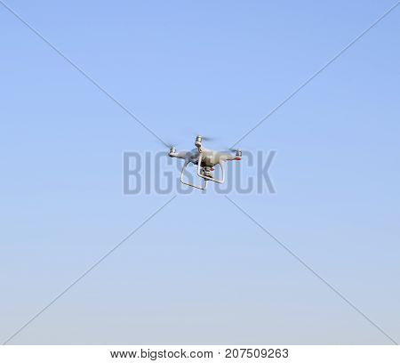 White drone against the blue evening sky. Multicopter flight