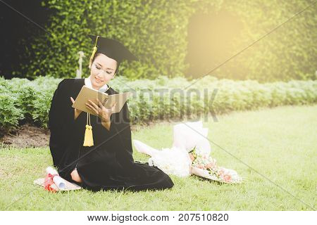 Graduate reading diary notebook in her hand feeling relaxing and so happiness in commencement day
