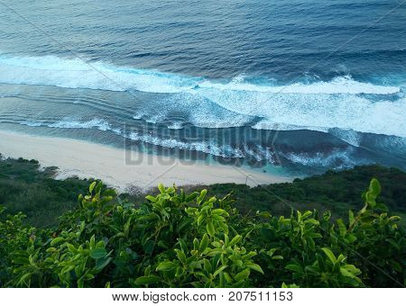 Top aerial view of beauty Bali beach. Empty paradise beach blue sea waves in Bali island Indonesia. Suluban and Nyang Nyang place. Sunset point