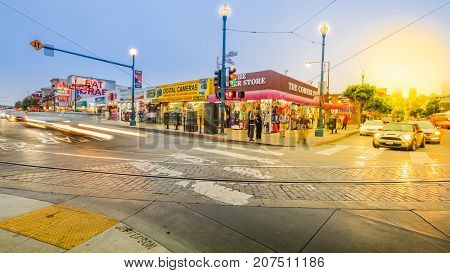 San Francisco, California, United States - August 14, 2016: Crossroad    on Jefferson and  Jones roads at sunset. Tourists, buses and cars in traffic. Holidays, lifestyle and nigthlife concept.